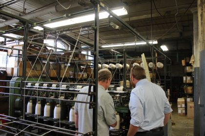 Rusty Vallee shows Sen. Libby how the company produces thread for their customers